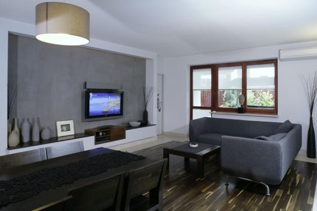 Minimalistyczny salon: betonowa ściana i szare kanapy