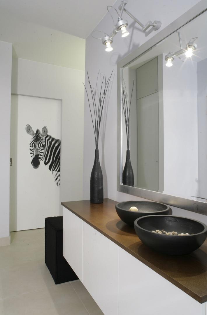 Jakaż ta zebra ciekawska! Tym razem zerka z drzwi do garderoby. Pewnie chciałaby się przejrzeć w zrobionym na wymiar lustrze, którego rama sprytnie udaje srebro. W rzeczywistości jest to drewno pomalowane na srebrny kolor i patynowane. Fot. Monika Filipiuk.