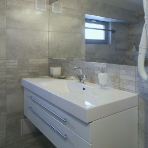 Podstawę, na której umieszczono umywalkę, stanowi wisząca szafka z dwiema szerokimi szufladami. Lica szuflad wykonano z białego, lakierowanego MDF-u. Wygodne otwieranie zapewniają szerokie relingi. Fot. Monika Filipiuk-Obałek.