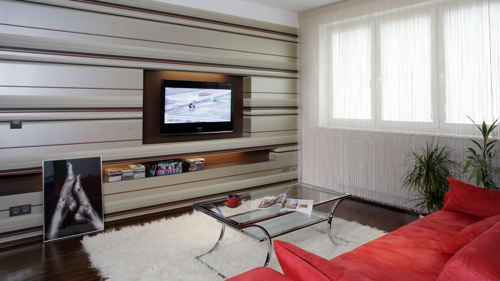 Dekoracyjna ściana optycznie poszerza powierzchnię salonu. Dzieje się tak za sprawą połyskującej tapety w poziome pasy (Harlequin). Fot. Monika Filipiuk.