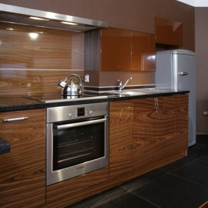 Zabudowa kuchenna pokryta fornirem z drewna (Santos modyfikowany) wraz czarnymi granitowymi blatami i frontami wiszących szafeczek z mdf-u, tworzy czystą i nowoczesną strefę. Fot. Monika Filipiuk.
