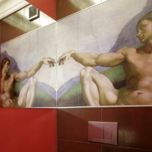 Nad umywalką, na całej długości ściany, zawieszono lustro. Odbija się w nim zaskakująca w tym miejscu dekoracja – reprodukcja fresku Michała Anioła z Kaplicy Sykstyńskiej. Metalizujące płytki (Iris Ceramika, seria Metal Line) kontrastują z rządzącą w łazience czerwienią, dodatkowo optycznie powiększając pomieszczenie. Fot. Monika Filipiuk.