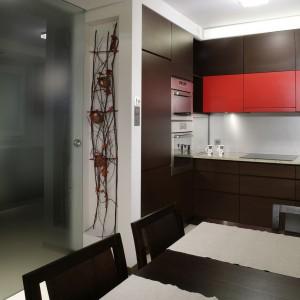 Oryginalna ozdoba, zawieszona na ścianie, jest pomysłem pani domu. Zabudowa kuchenna (robiona na zamówienie) zwraca uwagę czerwonym akcentem na frontach szafek. Fot. Monika Filipiuk.