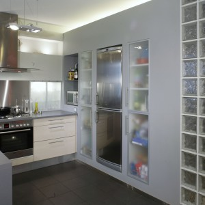 """Ścianka z luksferów jednocześnie rozjaśnia kuchnię i doświetla korytarz, a także zaaranżowane za nią, niewielkie """"pomieszczenie biurowe"""". Fot. Monika Filipiuk."""