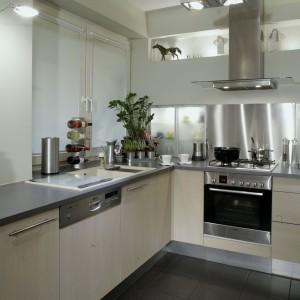 Rządzące w kuchni metaliczne szarości i gładkie fronty szafek, wykonane z mlecznego szkła, tworzą efekt sterylności. Odbijające się od nich światło reflektorków sufitowych i ściennych, oraz lampki halogenowe podświetlające wnętrze zabudowy i półeczek, rozświetlają pomieszczenie. Fot. Monika Filipiuk.