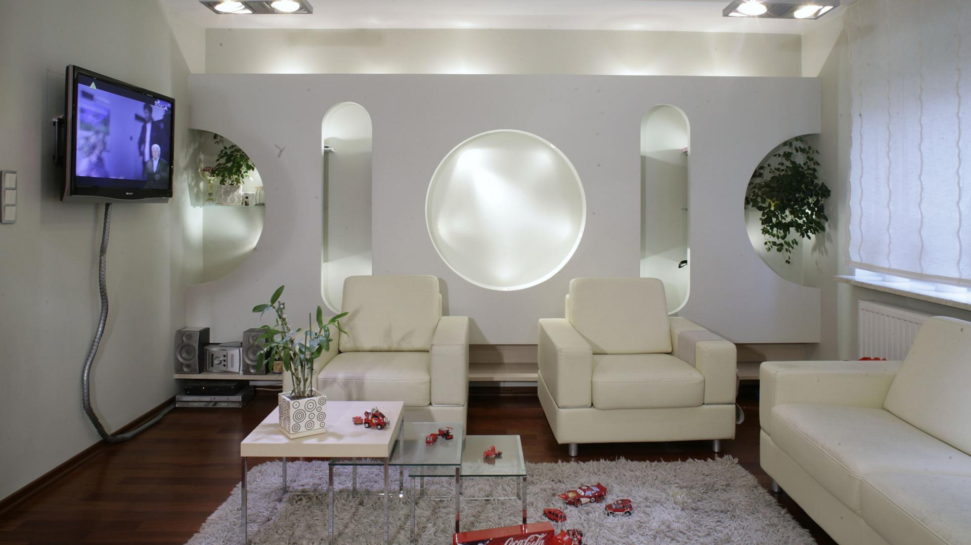 Półki zostały dyskretnie ukryte za geometrycznymi wcięciami w fantazyjnej ściance, a także za fotelami, tuż przy podłodze, na całej długości ściany. Dzięki temu w samym salonie jest o wiele więcej wolnego miejsca. Fot. Monika Filipiuk.