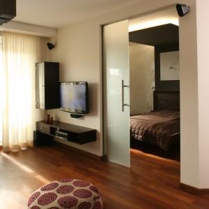 Sypialnia i salon zostały zaaranżowane w takich samych, przytulnych barwach, łączy je także ta sama podłoga - drewniany parkiet w ciepłym odcieniu. Fot. Bartosz Jarosz.