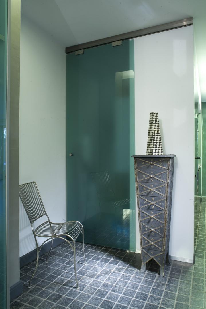 Indyjska szafka-trumienka kojarząca się z inną rzeczywistością, doskonale komponuje się z chłodnym, zdominowanym przez szkło, korytarzem. Fot. Bartosz Jarosz.