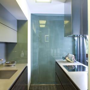 Tuż za salonikiem znajduje się kuchnia. Bardzo nowoczesna, minimalistyczna, z dużą ilością szkła. Fot. Bartosz Jarosz.