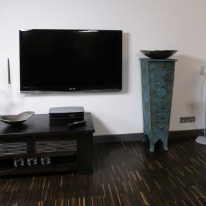 Nowoczesny ekran plazmowy, zawieszony bezpośrednio na ścianie, występuje w towarzystwie pochodzącej z Indii komódki, na której ustawiono sprzęt RTV. Fot. Bartosz Jarosz.
