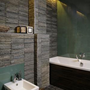 Blask światła, odbijający się w szkle, rozświetla łazienkę. Minimalistyczna bateria wannowa podkreśla nowoczesność wnętrza, a naturalne ozdoby, ciemna obudowa wanny i dywanik przydają mu charakteru i elegancji. Fot. Bartosz Jarosz.