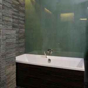 Ścianę przy wannie zabezpiecza tafla zielonego szkła, które oprócz wypełniania funkcji praktycznej, jest elementem dekoracyjnym w innych zakątkach łazienki. Fot. Bartosz Jarosz.