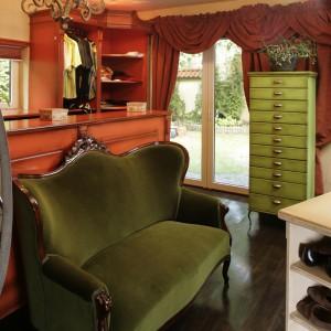 Obita zielonym pluszem kanapa oraz smukła, zielona komódka, to bardzo wytworny duet. Oba meble tworzą ciekawą kompozycję na tle szaf i zasłon w pomarańczowym kolorze. Fot. Bartosz Jarosz.
