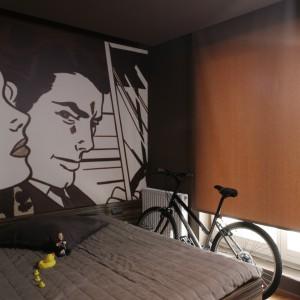 """Dominujący w sypialni spokojny, stonowany brąz działa wyciszająco. Nawet tapetowa reprodukcja Roy\\\'a Lichtensteina, która w oryginale jest barwna, tutaj """"przebrała się"""" w brąz. Fot. Bartosz Jarosz."""