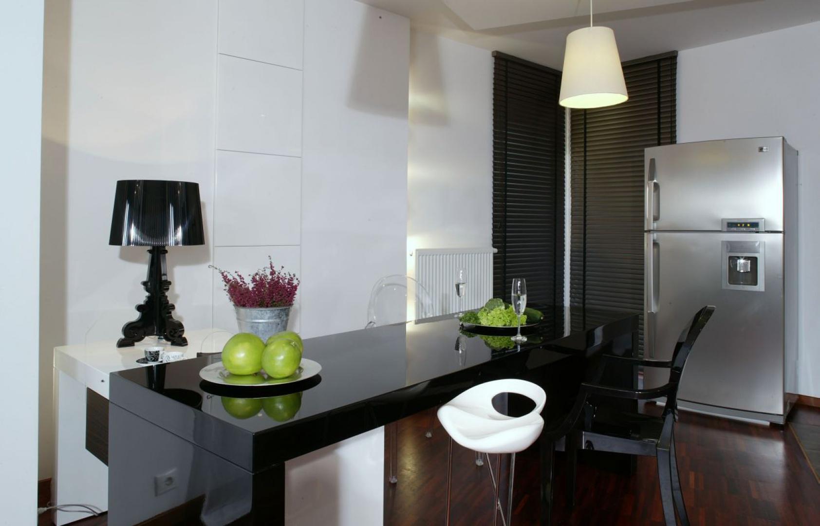 Czarno-biały stół jadalniany, wykonany na zamówienie z płyty MDF na wysoki połysk, ma bardzo ciekawą konstrukcję. Jego biała część jest mobilna – w zależności od potrzeb można ją przesunąć w dowolne miejsce. Fot. Monika Filipiuk.