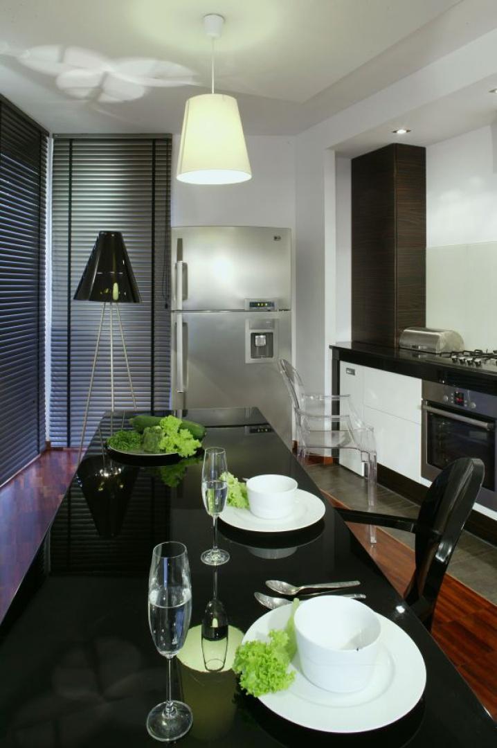 W aneksie kuchennym dominują oryginalna bryła stołu, wykonanego na zamówienie z lakierowanego na wysoki połysk MDF-u, oraz imponujących rozmiarów -lodówka firmy LG Electronics. Fot. Monika Filipiuk.