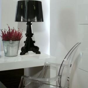 Dodatki, które nadają ostateczny kształt całości, to przezroczyste krzesło projektu Philippe Starcka oraz czarna stylowa lampa zaprojektowana przez Ferruccio Laviani. Oba produkty pochodzą z oferty firmy Kartell. Fot. Monika Filipiuk.