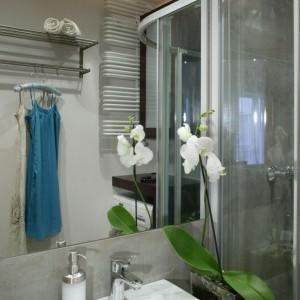 Koło umywalki ustawiono kwiat w maksymalnie prostym, wykonanym z czystego szkła, wazonie. Fot. Monika Filipiuk.