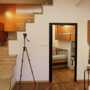 Schody w górę to kolejny żart architekta. Prowadzą donikąd. Wyżej nie ma już  żadnego pomieszczenia. Pod nimi, od korytarza, biegną schody w dół do sypialni gospodarzy. Tutaj zaś, po wyjściu na spocznik, uzyskuje się dostęp do podsufitowej garderoby z ukrytym systemem wnęk i półek.  Fot. Bartosz Jarosz.
