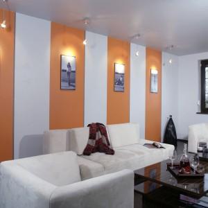 Głównym atutem salonu jest oryginalna galeria fotografii, zaaranżowana na jednej ze ścian. Czarno-białe zdjęcia autorstwa właścicielki, wyeksponowano na pomarańczowych pasach i starannie podświetlono. Fot. Monika Filipiuk.