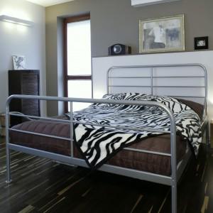 Podłogę w sypialni wyłożono tym samym co w salonie, nieco egzotycznym, parkietem z dębu afrykańskiego. Drewniane, przeszklone drzwi, zostały zaprojektowane specjalnie do tego wnętrza. Fot. Monika Filipiuk.
