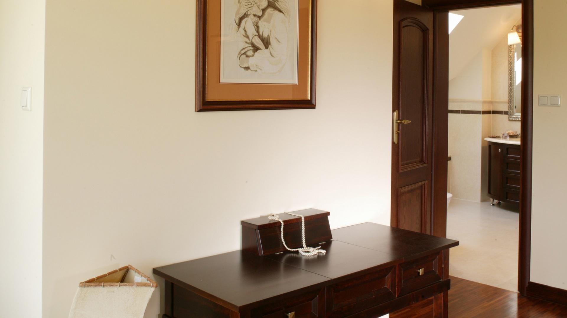 Obok niedużego sekretarzyka stoi charakterystyczna lampa, przypominająca antyczny żagiel. Pozłacane kinkiety, umieszczone nad sekretarzykiem, oświetlają wyhaftowany przez panią domu obrazek. Fot. Monika Filipiuk.