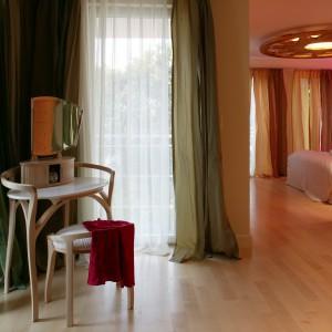 Sypialnia sąsiaduje z domowym ciągiem komunikacyjnym, który wieńczy toaletka pani domu. O klimat tej części mieszkania zadbały również oliwkowozielone zasłony, wykonane z takiego samego materiału, jak te w strefie snu. Fot. Tomek Markowski.