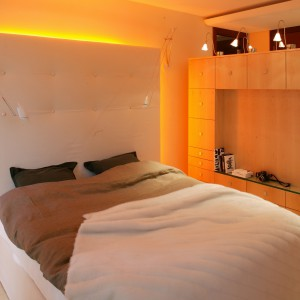 Sypialnię od pozostałych pomieszczeń odgradza dwustronna meblościanka, oświetlona dodatkowo kilkoma lampami w kształcie kwiatów. Wysoki zagłówek łóżka, zakrywający instalację świetlną, powiela sposób wykończenia szafy. Fot. Tomek Markowski.