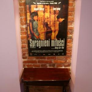 Surowe cegły stworzyły atrakcyjne tło dla plakatu z nastrojowego filmu Wong Kar-Waia i jednego z odziedziczonych po przodkach stolików. Oświetlenie? Najprostsze z możliwych – dwie halogenowe lampki. Fot. Paweł Supernak.