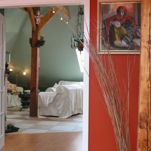 Z pomarańczową sypialnią sąsiaduje salon utrzymany w zupełnie odmiennej kolorystyce. Chłodne barwy zieleni i białe pokrowce na meblach świadczą o tym, że gospodarze tego domu cenią sobie różnorodność. Fot. Tomek Markowski.