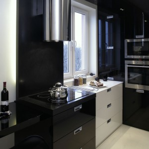 Kuchnia oparta jest na kontraście bieli i czerni, co dodaje elegancji i wyznacza poszczególne strefy w tym pomieszczeniu. Kolor czarny zarezerwowany został dla miejsc, w których gotujemy. Fronty i blaty tworzą jednolitą bryłę. Fot. Monika Filipiuk.