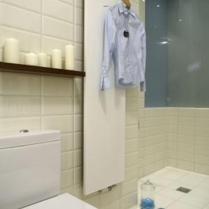 Za szkłem, które jest także widoczne od strony salonu, znajduje się deszczownica  podświetlona od góry halogenami, która, jak podkreśla właścicielka – zapewnia olbrzymią frajdę. Grzejnik (Vasco) dopasował się natomiast do pozostałych kwadratowych form w łazience. Fot. Monika Filipiuk.