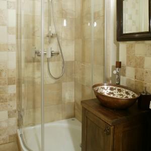 Ścianę w okolicy kabiny prysznicowej wyłożono płytkami z trawertynu. Specyficzna, nierównomierna struktura płytek doskonale wpisuje się w panującą tu stylistykę. Punktem centralnym w łazience gościnnej jest przywieziona z Meksyku nablatowa umywalka w kształcie misy. Fot. Monika Filipiuk.