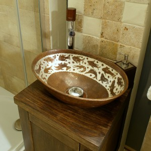 Bateria z uchwytem z drewna orzechowego świetnie pasuje do brązowej ceramicznej misy i wybarwionej na orzech szafki. Wyprodukowała ją firma Tres. Fot. Monika Filipiuk.