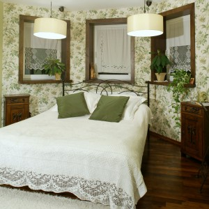 W sypialni małżeńskiej również postawiono na południowe klimaty, stonowane kolory ziemi i rustykalne detale. Zielonkawy kolor roślinnego wzoru na tapecie, stał się inspiracją do aranżacji pozostałych fragmentów ścian oraz ozdabiających obszerne łoże poduszek (Dekoria). Fot. Monika Filipiuk.