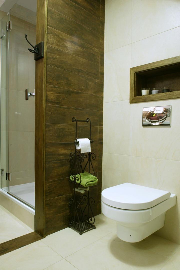 Kinkiet, stojak na papier i ręczniki (Art-Galerie) oraz wieszak (Meble Indyjskie) współtworzą elegancki, lekko rustykalny klimat wnętrza. Fot. Monika Filipiuk.