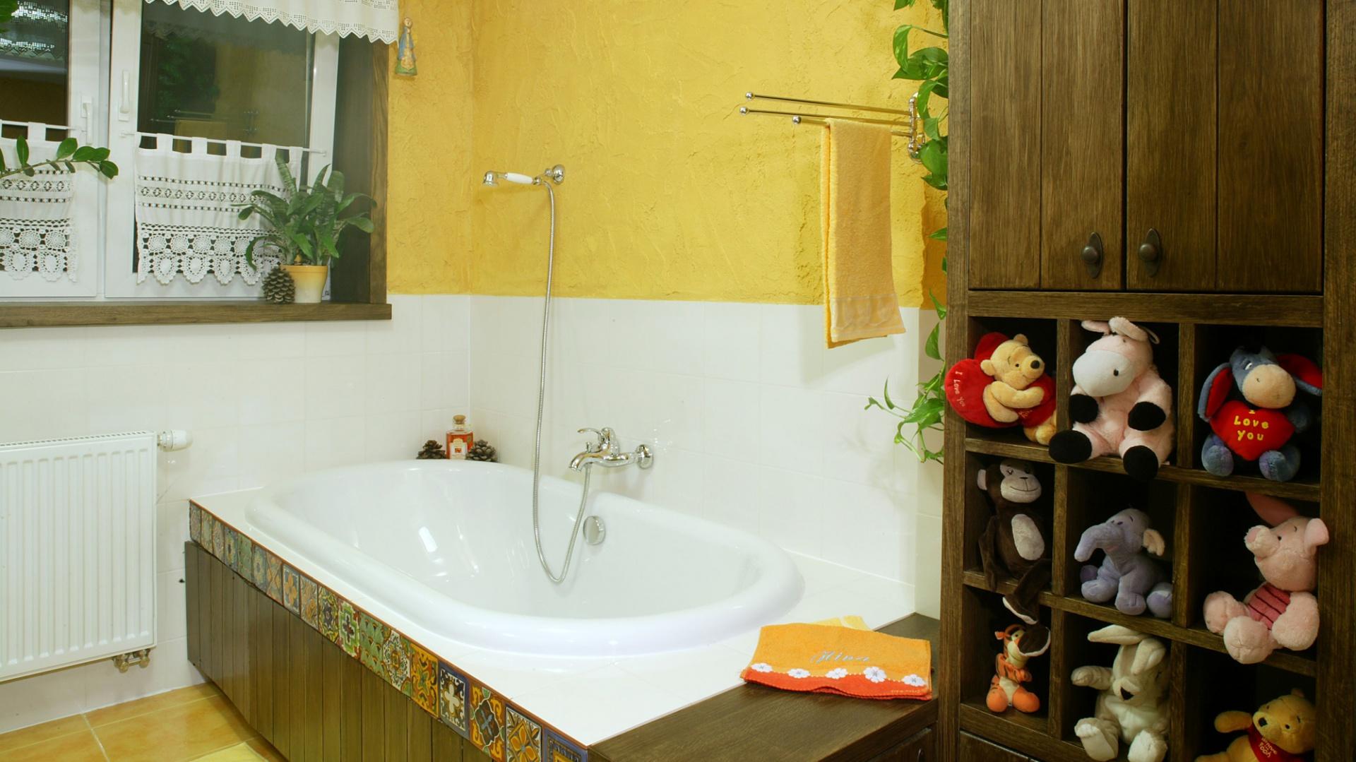 W drewnianej obudowie wanny, oprócz meksykańskich dekorów, znajduje się dyskretna szafka. Duży kredens obok może pomieścić nie tylko maskotki. Fot. Monika Filipiuk.