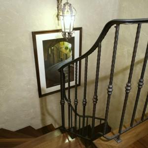 Wiodące na piętro schody to przejaw fascynacji Grecją. Ręcznie kuta balustrada (Almet), mimo stalowej konstrukcji przypomina wątłą, powyginaną winną latorośl. Klimat budują tu też starannie dobrane, stylowe dodatki czy reprodukcje obrazów Alfonsa Muchy. Fot. Monika Filipiuk.