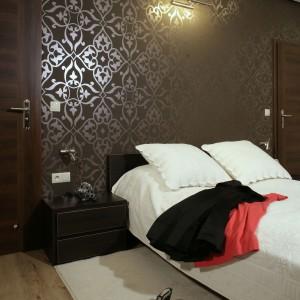 Dość ciemne, dominujące we wnętrzu tonacje, zostały zrównoważone przez jaśniejsze elementy: białe ściany, jasny parkiet na podłodze, białą, wzorzystą narzutę na łóżko i miękki, przytulny dywan w kolorze écru. Fot. Monika Filipiuk.
