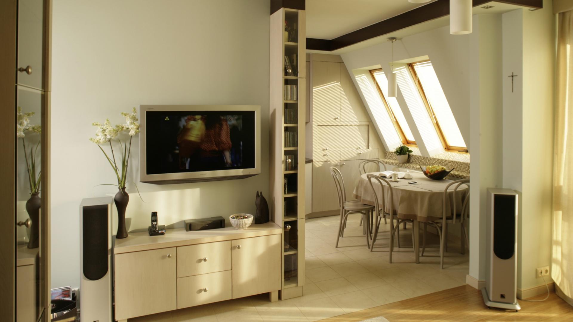Ścianka, przy której znajduje się kącik RTV, przesłania prawie całą kuchnię. Meble salonowe są wykonane z tych samych materiałów, co kuchenne. Identyczne są też metalowe uchwyty. Fot. Bartosz Jarosz.