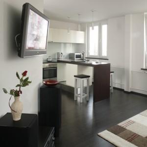 Podłogę w całym mieszkaniu wyłożono przepięknymi panelami, które wspaniale komponują się z wenge i bielą, przydając wnętrzom elegancji. Fot. Bartosz Jarosz.
