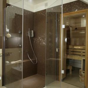 Bezbrodzikowa kabina prysznicowa, z wyprofilowanym wygodnym siedziskiem, sąsiaduje bezpośrednio z przesłoniętą szklanymi drzwiami sauną. Fot. Monika Filipiuk.