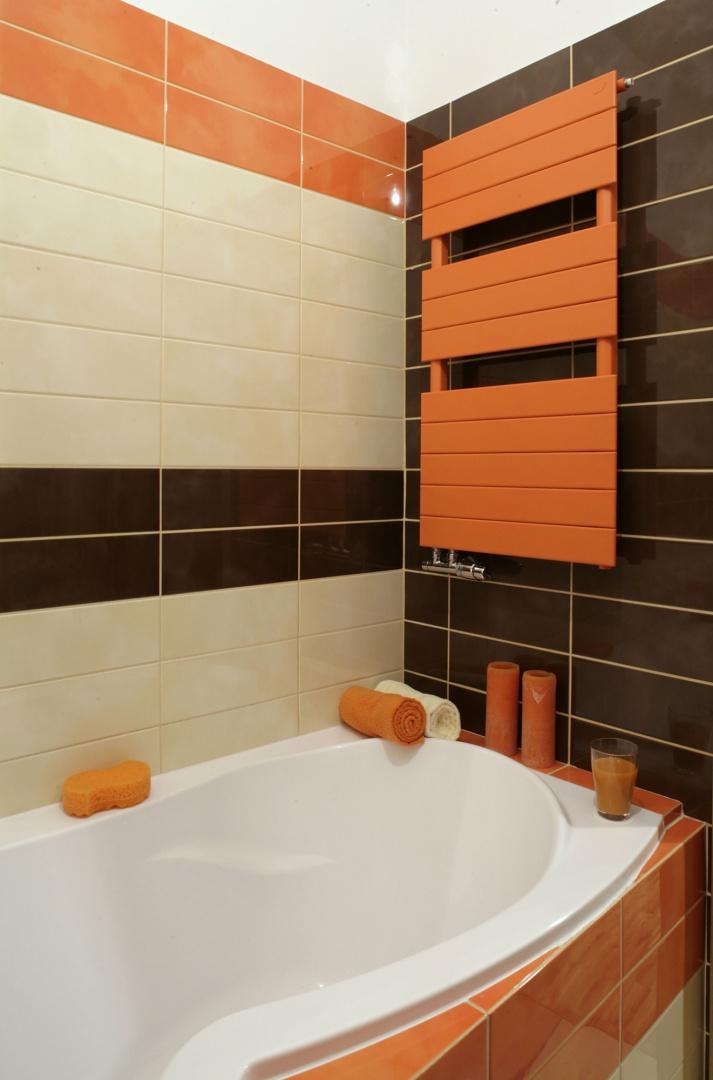 Łazienka to konsekwentnie poprowadzona gra form i kolorów. Pomarańczowy jest nawet kaloryfer. A jego kształt powiela prostokątną formę płytek. Fot. Monika Filipiuk.