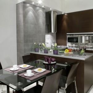 Uroku kuchni i jadalni dodają fioletowe dodatki: doniczki na kwiatki, podkładki pod naczynia i świece. Sprzęty kuchenne, zainstalowane w zabudowie, pochodzą z firmy Siemens. Okap natomiast to Faber.
