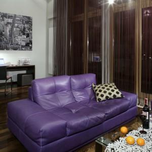 Podłoga salonu została wyłożona klepkami z deski dębowej, poddanej obróbce termicznej, dzięki czemu każda klepka zyskała inny, oryginalny odcień. W wysokich oknach zawieszono sznurkowe zasłony w fioletowym kolorze (tzw. makarony). Fot. Monika Filipiuk.