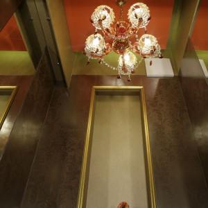 Efektowny żyrandol, żółta szafka i umywalka w kolorze pomarańczowym są mocnymi akcentami, które z całym wystrojem łazienki tworzą idealne połączenie.