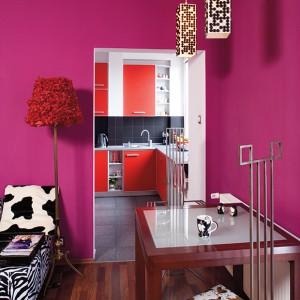 Kuchnia jest nowoczesna, odcina się stylistycznie od salonu. Rządzą w niej biele, szarości i odważna czerwień. Fot. Bartosz Jarosz.