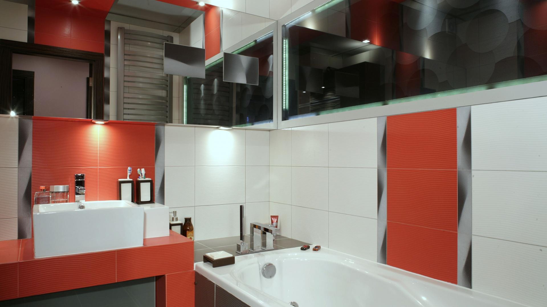 Łazienkę dodatkowo powiększa sufit podwieszany – i to nie byle jaki! Granicę między nim a płytkami zatarto poprzez naklejenie cienkich lustrzanych pasów. Fot. Monika Filipiuk.