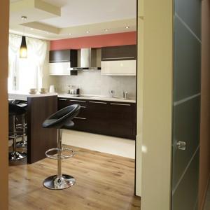 Z holu do kuchni prowadzą przesuwne drzwi ze szkła satynowego. Na podłodze dwa materiały: panele i gres (Ceramiki Paradyż). Fot. Bartosz Jarosz.