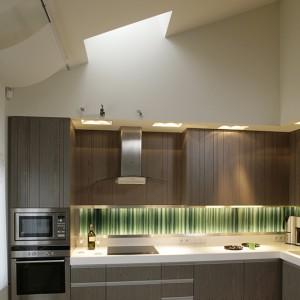 Dzięki oknom, znajdującym się w skosie dachowym, do kuchni wpadają wiązki naturalnego światła. Dodatkowo – punktowe oświetlenie blatów roboczych i efektowna wisząca lampa. Fot. Bartosz Jarosz.